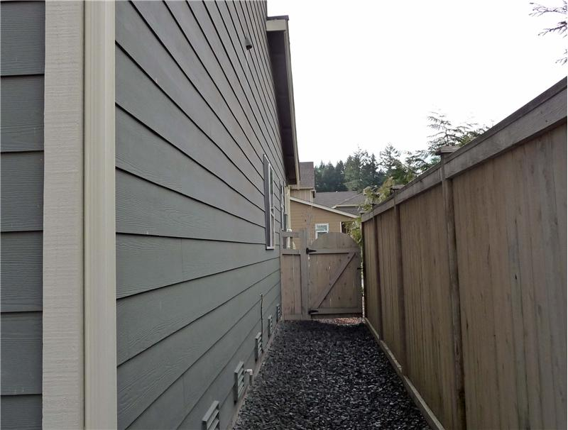 Side of townhome recently gravelled back to gate.