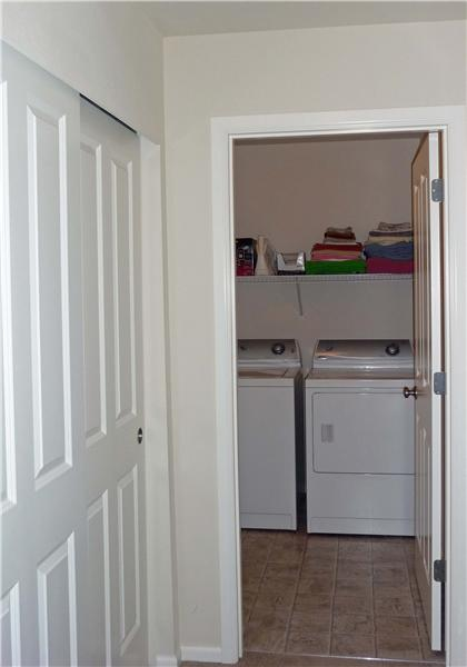 Convenient upstairs utilty with shelving plus double storage closet nearby.