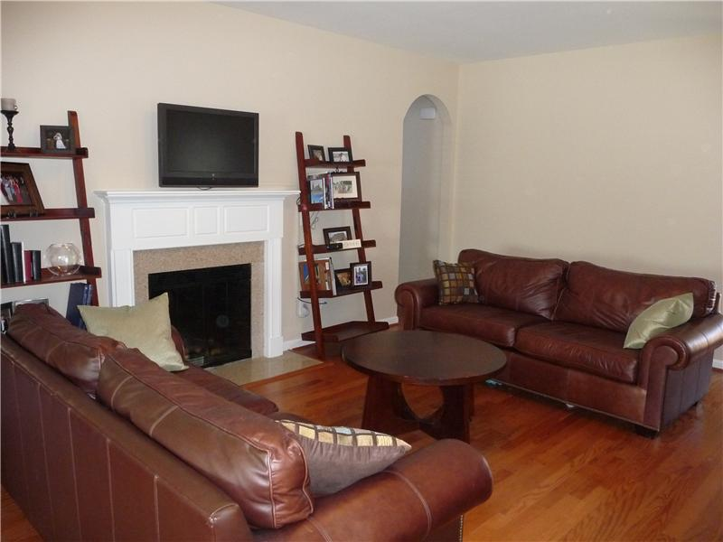 Great room has pretty hardwood flooring and a fireplace.