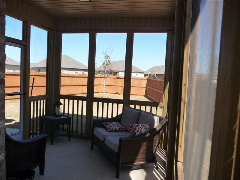 Screened porch and view of back yard and privacy fence.