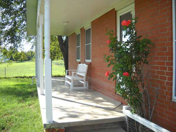 Sip some tea on the lovely covered front porch, relax and smell the roses