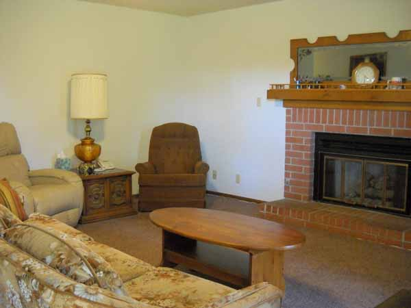 Large living area with ceiling fan and brick fireplace with gas starter and glass doors