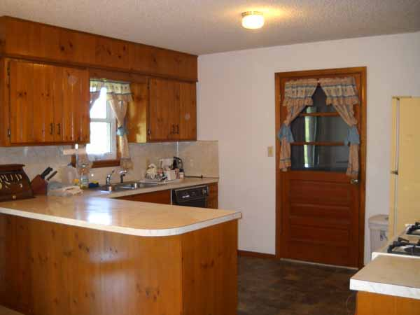 Doorway in kitchen leads to attached 2-car garage with storm cellar, workbenches