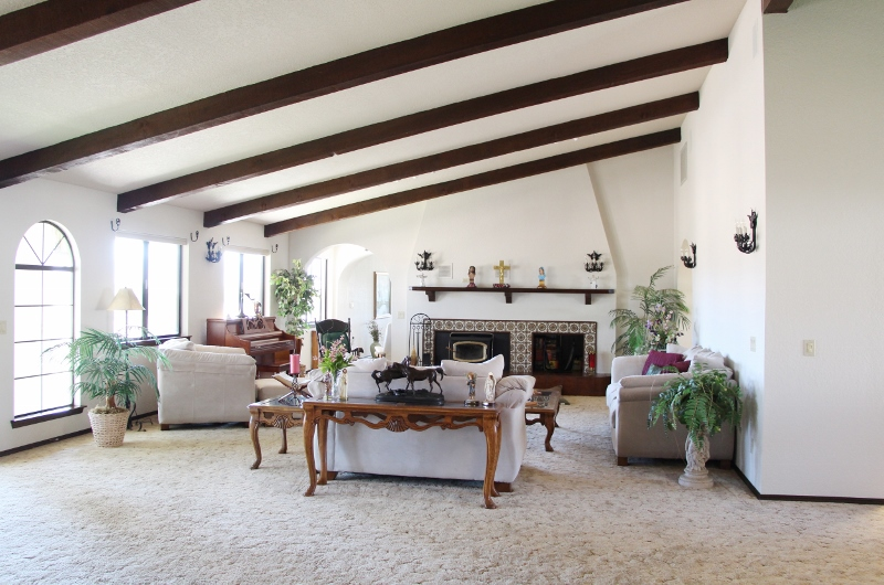 Living room with vaulted wood beamed ceilings and wood burning fireplace