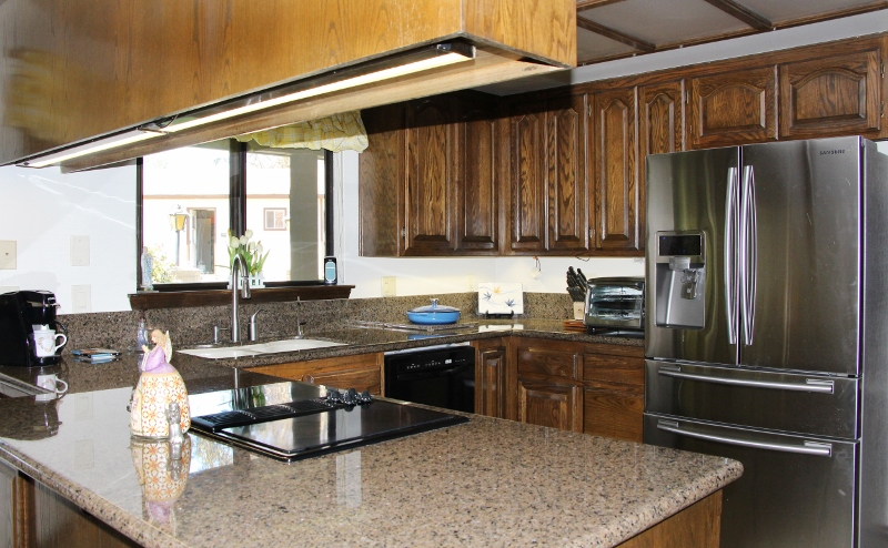 Kitchen with granite counter tops, built in microwave, and tile floors