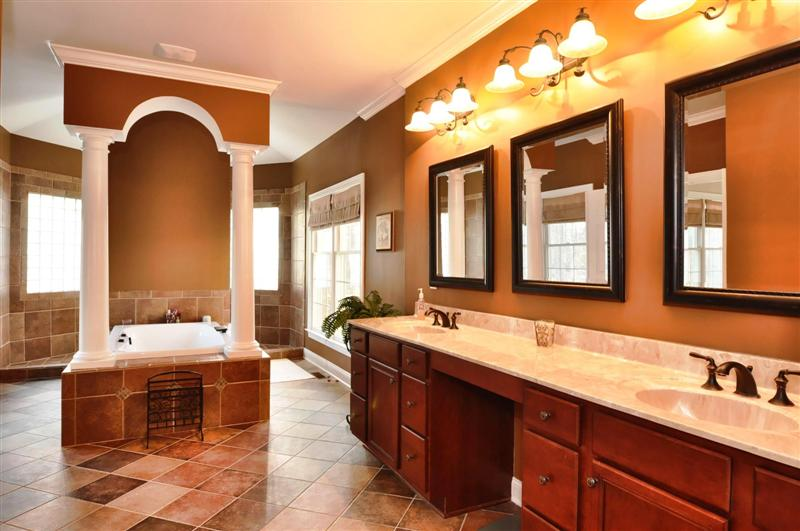 Luxurious master bathroom has dual granite vanities with an oversized walk-through custom shower and tile