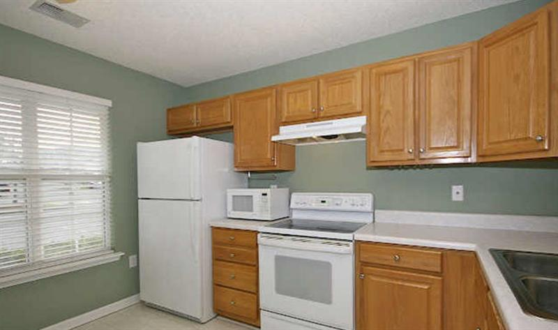 Kitchen has white appliances including an electric cooktop self cleaning oven, table top microwave oven and refrigerator